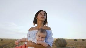 La mujer joven atractiva lleva al pequeño hijo alrededor de campo en sus brazos en la puesta del sol Mamá y bebé en un paseo de l almacen de metraje de vídeo