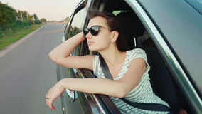 La mujer joven atractiva mira hacia fuera la ventanilla del coche Sueño de viajar almacen de metraje de vídeo