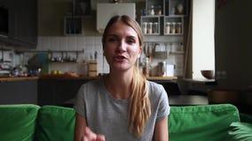 La mujer joven atractiva que habla mirando el webcam hace la llamada video almacen de metraje de vídeo