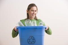 La mujer joven atractiva que sostiene un azul recicla el compartimiento Foto de archivo libre de regalías