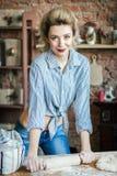 La mujer joven atractiva rubia prepara la pasta en la cocina ama de casa con los bolsos de la harina y con el rodillo en la cocin imagenes de archivo