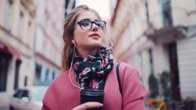 La mujer joven atractiva se coloca en la calle de la ciudad con una taza de café, escuchando la música con los auriculares y la m metrajes
