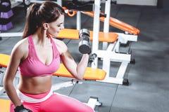 La mujer joven atractiva se está resolviendo con pesas de gimnasia en gimnasio fotos de archivo