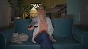 La mujer joven, atractiva se sienta con una taza en un sof? al gato y da vuelta en la televisi?n usando un teledirigido 4K almacen de video