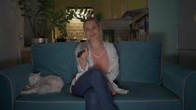 La mujer joven, atractiva se sienta con una taza en un sof? al gato y da vuelta en la televisi?n usando un teledirigido 4K almacen de metraje de vídeo