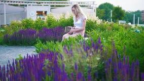 La mujer joven atractiva vino al jardín con las flores y se sentó para leer un libro metrajes