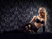 La mujer joven, atractiva y hermosa en ropa interior en la cama encima enría Fotos de archivo libres de regalías