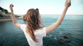 La mujer joven aumentó su mano hasta el sol, contra el mar, las rocas y el cielo con las nubes almacen de video
