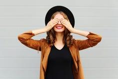La mujer joven bastante fresca de la moda cierra la sonrisa linda de los ojos llevando una chaqueta elegante del marrón del sombr Fotografía de archivo libre de regalías