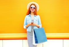 La mujer joven bastante sonriente de la moda está utilizando el smartphone Imagen de archivo libre de regalías