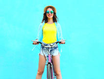 La mujer joven bastante sonriente monta una bicicleta sobre azul colorido Imagen de archivo libre de regalías