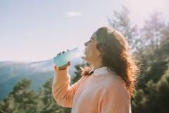 La mujer joven bebe el agua en el medio de la montaña imagenes de archivo