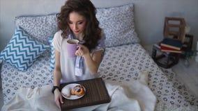 La mujer joven bebe el café de la mañana y las empanadas desayunan en el dormitorio metrajes