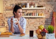 La mujer joven bebe el café del desayuno en pijama imagen de archivo