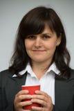 La mujer joven bebe el café o el té imagenes de archivo
