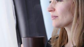 La mujer joven bebe el café o el té cerca de la ventana 4K almacen de video