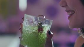La mujer joven bebe las fresas adornadas cóctel verde con un vidrio y una sonrisa transparentes en el primer de la noche metrajes