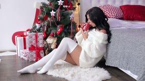 La mujer joven bebe té cerca de un árbol de navidad almacen de metraje de vídeo