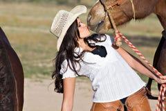 La mujer joven besa su caballo Imagenes de archivo