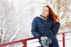 La mujer joven bien proporcionada tiene un resto en el parque del invierno Imagenes de archivo