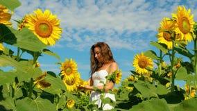 La mujer joven bonita del retrato con el pelo rizado largo del coñac se coloca en campo con los girasoles jovenes y la corre para metrajes