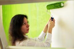 La mujer joven bonita en una camisa blanca está pintando cuidadosamente la pared interior verde con el rodillo en un nuevo hogar fotografía de archivo