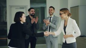 La mujer joven bonita está consiguiendo trabajo en la compañía acertada que sacude las manos con el CEO y que sonríe mientras que almacen de metraje de vídeo
