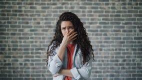 La mujer joven bonita está sosteniendo la nariz debido a olor de disgusto y está frunciendo el ceño metrajes