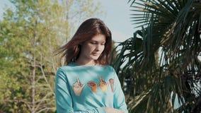 La mujer joven, bonita se vistió en paseos de moda de una camiseta a través del parque almacen de video