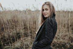 La mujer joven bonita y sofisticada con el pelo rubio largo se vistió en capa de las lanas Fotografía de archivo