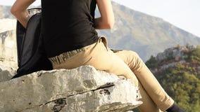 La mujer joven busca algo en la mochila que se sienta al borde del acantilado de la montaña contra los picos de montañas hermosos metrajes