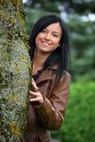 La mujer joven cómoda mira hacia fuera de detrás un árbol Imagen de archivo