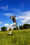 La mujer joven cae en el aire en un prado de la flor Imagenes de archivo