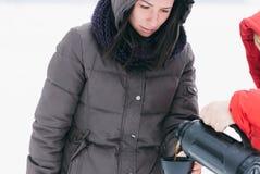 La mujer joven calentó invierno caliente del café de la taza imagenes de archivo
