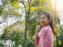 La mujer joven calienta a su cuerpo estirando sus brazos para estar lista para ejercitar y para hacer yoga en el parque Imágenes de archivo libres de regalías