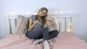 La mujer joven cambia los canales de televisión en el telecontrol almacen de video