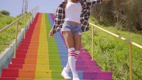 La mujer joven camina abajo de las escaleras coloridas almacen de video