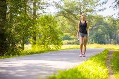 La mujer joven camina al aire libre y escucha la música Imagenes de archivo