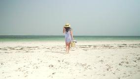 La mujer joven camina descalzo en la playa hacia el océano almacen de video