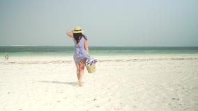 La mujer joven camina descalzo en la playa hacia el océano almacen de metraje de vídeo