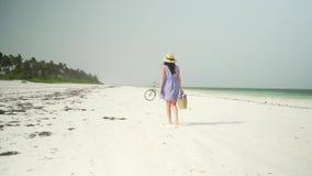 La mujer joven camina descalzo en la playa a lo largo del océano metrajes