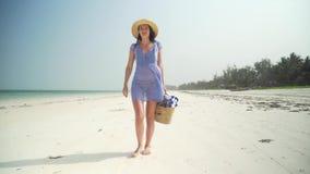 La mujer joven camina descalzo en la playa a lo largo del océano almacen de video