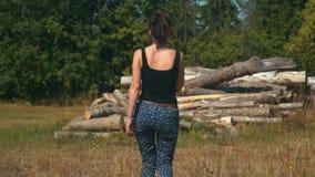 La mujer joven camina lentamente el campo de oro hacia registros y bosque conífero almacen de video