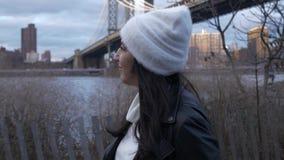 La mujer joven camina a lo largo de Hudson River en el puente de Brooklyn Nueva York metrajes