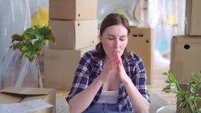 La mujer joven cansada del retrato entre las cajas a moverse, lee el problema del dinero del documento de orden de desahucio almacen de metraje de vídeo