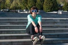 La mujer joven cansada en gafas de sol divertidas se sienta en los pasos en el p Foto de archivo libre de regalías