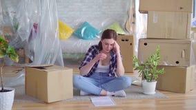 La mujer joven cansada entre las cajas a moverse, lee los documentos para el desahucio almacen de metraje de vídeo