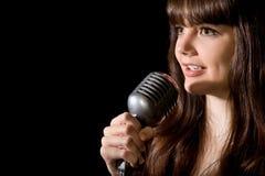 La mujer joven canta en el micrófono aislado en negro Foto de archivo libre de regalías