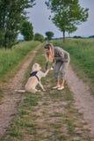 La mujer joven cariñosa ofreció una pata por su perro casero imagenes de archivo