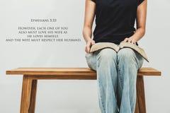 La mujer joven casual sostiene un 5:33 abierto de Ephesians de la biblia en su revestimiento Foto de archivo libre de regalías
